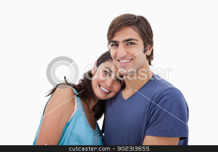 Lovely couple embracing each other stock photo, Lovely couple embracing each other against a white background by Wavebreak Media