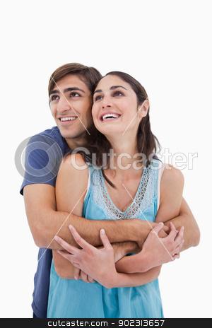 Portrait of an in love couple embracing each other stock photo, Portrait of an in love couple embracing each other against a white background by Wavebreak Media