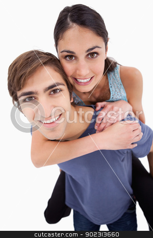 Portrait of a young man holding his girlfriend on his back stock photo, Portrait of a young man holding his girlfriend on his back against a white background by Wavebreak Media