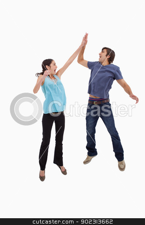 Portrait of a couple jumping together stock photo, Portrait of a couple jumping together against a white background by Wavebreak Media