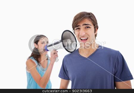 Woman yelling at her boyfriend through a megaphone stock photo, Woman yelling at her boyfriend through a megaphone against a white background by Wavebreak Media