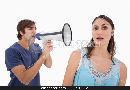 Man yelling at her girlfriend through a megaphone stock photo, Man yelling at her girlfriend through a megaphone against a white background by Wavebreak Media