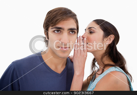 Woman whispering something to her fiance stock photo, Woman whispering something to her fiance against a white background by Wavebreak Media