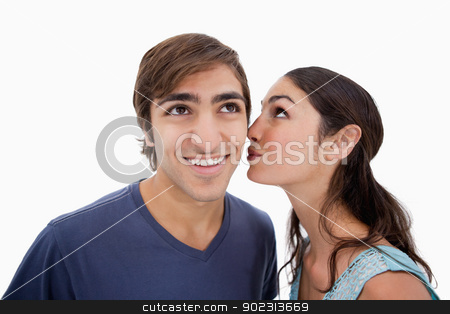 Lovely woman whispering something to her fiance stock photo, Lovely woman whispering something to her fiance against a white background by Wavebreak Media