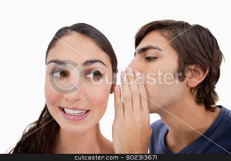 Man whispering something to his fiance stock photo, Man whispering something to his fiance against a white background by Wavebreak Media