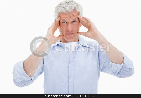 Mature man having a headache stock photo, Mature man having a headache against a white background by Wavebreak Media