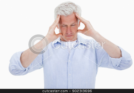 Exhausted man having a headache stock photo, Exhausted man having a headache against a white background by Wavebreak Media