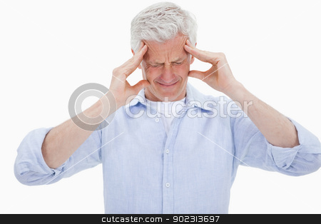 Exhausted man having a strong headache stock photo, Exhausted man having a strong headache against a white background by Wavebreak Media
