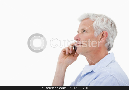 Side view of a man making a phone call stock photo, Side view of a man making a phone call against a white background by Wavebreak Media