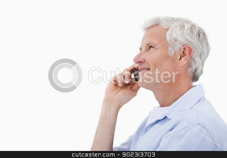 Side view of a smiling mature man making a phone call stock photo, Side view of a smiling mature man making a phone call against a white background by Wavebreak Media