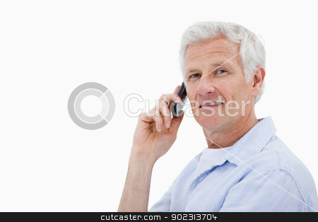 Side view of a man making a phone call while looking at the came stock photo, Side view of a man making a phone call while looking at the camera against a white background by Wavebreak Media