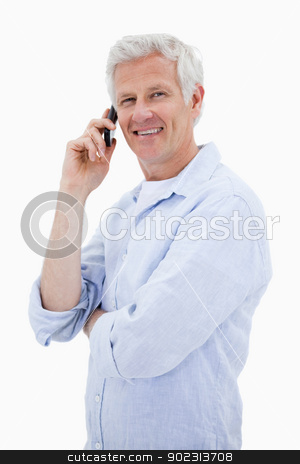 Portrait of a happy man making a phone call while looking at the stock photo, Portrait of a happy man making a phone call while looking at the camera against a white background by Wavebreak Media