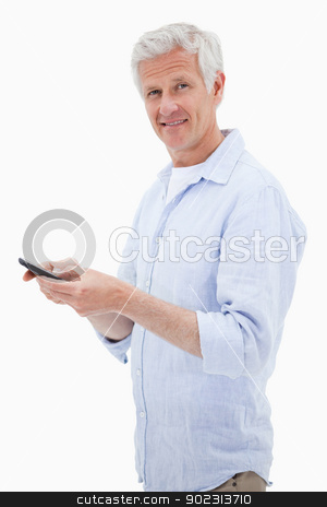 Portrait of a man using his mobile phone while looking at the ca stock photo, Portrait of a man using his mobile phone while looking at the camera against a white background by Wavebreak Media