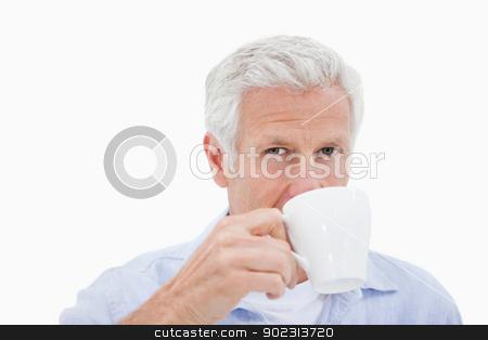 Mature man drinking tea stock photo, Mature man drinking tea against a white background by Wavebreak Media