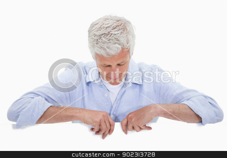 Portrait of a man standing behind blank panel stock photo, Portrait of a man standing behind blank panel against a white background by Wavebreak Media
