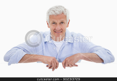 Portrait of a smiling mature man standing behind blank panel stock photo, Portrait of a smiling mature man standing behind blank panel against a white background by Wavebreak Media