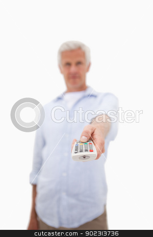 Portrait of a mature man using a remote stock photo, Portrait of a mature man using a remote against a white background by Wavebreak Media