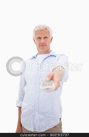 Portrait of a mature man switching of channel stock photo, Portrait of a mature man switching of channel against a white background by Wavebreak Media