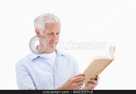 Man reading a book stock photo, Man reading a book against a white background by Wavebreak Media