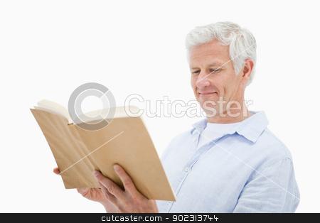Happy mature man reading a book stock photo, Happy mature man reading a book against a white background by Wavebreak Media