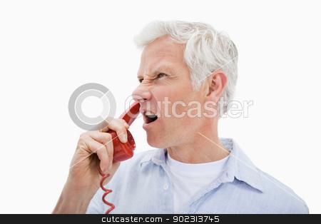 Angry man making a phone call stock photo, Angry man making a phone call against a white background by Wavebreak Media