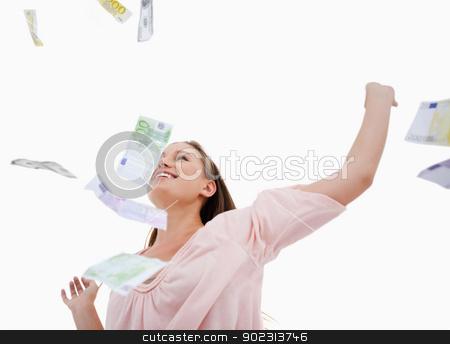 Woman under bank notes falling stock photo, Woman under bank notes falling against a white background by Wavebreak Media
