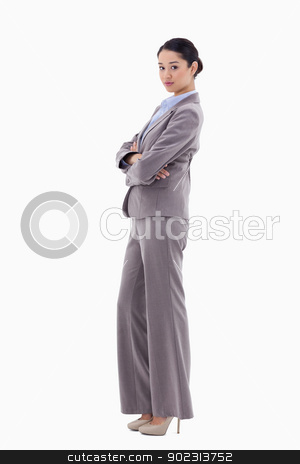 Portrait of a brunette businesswoman posing with the arms crosse stock photo, Portrait of a brunette businesswoman posing with the arms crossed against a white background by Wavebreak Media