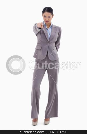 Portrait of a brunette businesswoman pointing at the viewer stock photo, Portrait of a brunette businesswoman pointing at the viewer against a white background by Wavebreak Media