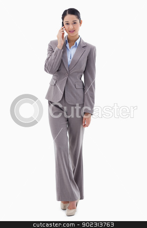 Portrait of a young businesswoman making a phone call stock photo, Portrait of a young businesswoman making a phone call against a white background by Wavebreak Media