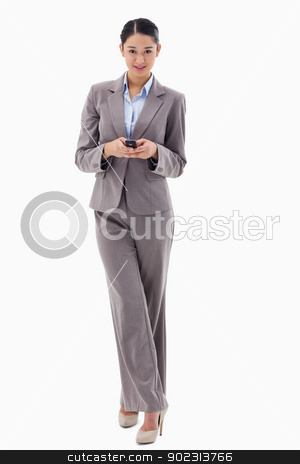 Portrait of a smiling brunette businesswoman sending a text mess stock photo, Portrait of a smiling brunette businesswoman sending a text message against a white background by Wavebreak Media