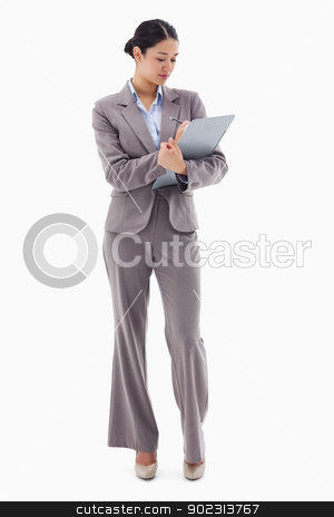 Portrait of a businesswoman taking notes stock photo, Portrait of a businesswoman taking notes against a white background by Wavebreak Media