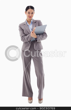 Portrait of a brunette businesswoman taking notes stock photo, Portrait of a brunette businesswoman taking notes against a white background by Wavebreak Media