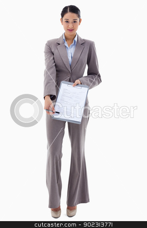 Portrait of a smiling businesswoman showing a contract stock photo, Portrait of a smiling businesswoman showing a contract against a white background by Wavebreak Media