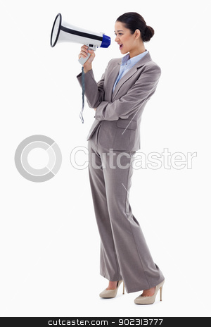 Portrait of a businesswoman shouting through a megaphone stock photo, Portrait of a businesswoman shouting through a megaphone against a white background by Wavebreak Media
