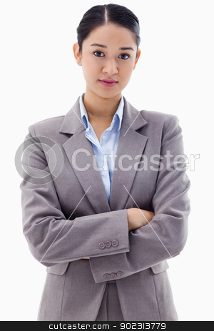 Portrait of a serious brunette businesswoman posing with the arm stock photo, Portrait of a serious brunette businesswoman posing with the arms crossed against a white background by Wavebreak Media
