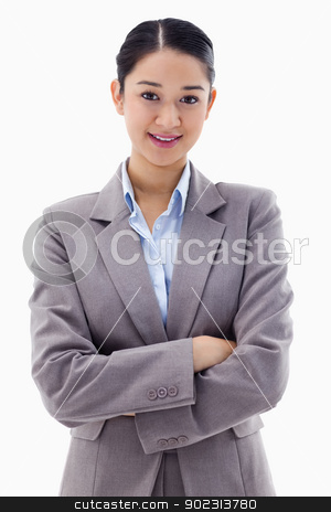 Portrait of a smiling brunette businesswoman posing with the arm stock photo, Portrait of a smiling brunette businesswoman posing with the arms crossed against a white background by Wavebreak Media