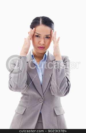 Portrait of a gorgeous businesswoman having a headache stock photo, Portrait of a gorgeous businesswoman having a headache against a white background by Wavebreak Media