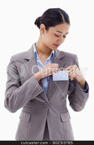 Portrait of a businesswoman clipping her badge stock photo, Portrait of a businesswoman clipping her badge against a white background by Wavebreak Media