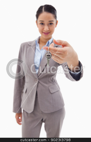 Portrait of a businesswoman holding a key stock photo, Portrait of a businesswoman holding a key against a white background by Wavebreak Media