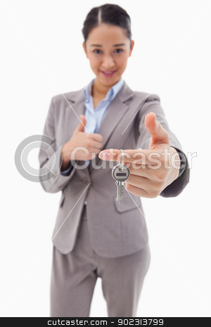 Portrait of a businesswoman holding a key with the thumb up stock photo, Portrait of a businesswoman holding a key with the thumb up against a white background by Wavebreak Media