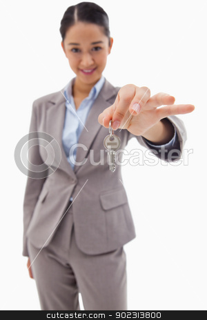 Portrait of a smiling businesswoman holding a key stock photo, Portrait of a smiling businesswoman holding a key against a white background by Wavebreak Media