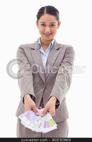 Portrait of a businesswoman showing bank notes stock photo, Portrait of a businesswoman showing bank notes against a white background by Wavebreak Media