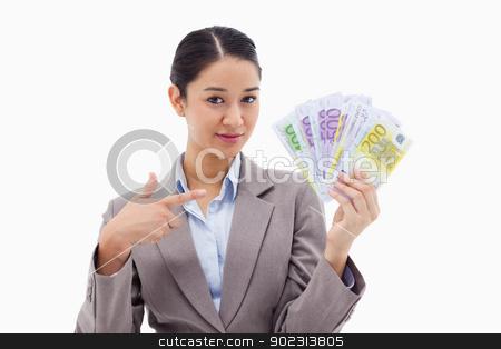 Businesswoman holding bank notes stock photo, Businesswoman holding bank notes against a white background by Wavebreak Media
