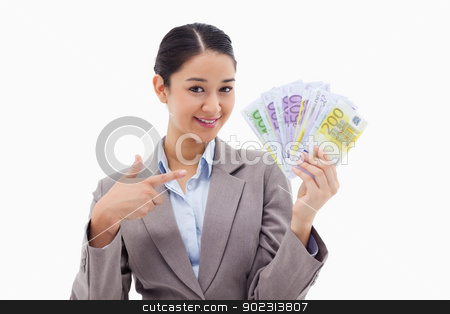 Smiling businesswoman holding bank notes stock photo, Smiling businesswoman holding bank notes against a white background by Wavebreak Media