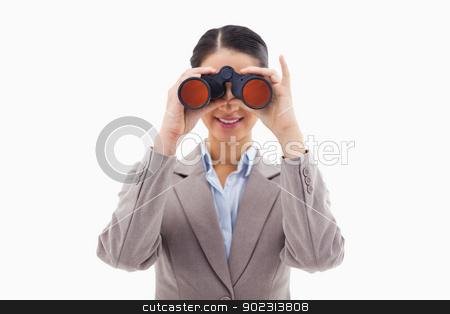 Businesswoman looking through binoculars stock photo, Businesswoman looking through binoculars against a white background by Wavebreak Media