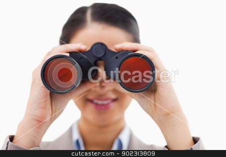 Close up of a businesswoman looking through binoculars stock photo, Close up of a businesswoman looking through binoculars against a white background by Wavebreak Media