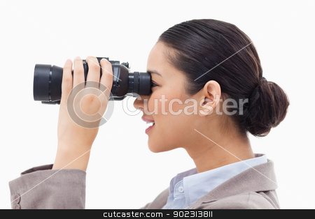 Side view of a businesswoman looking through binoculars stock photo, Side view of a businesswoman looking through binoculars against a white background by Wavebreak Media