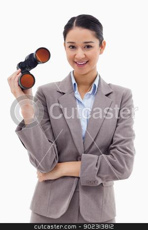 Portrait of a businesswoman holding binoculars stock photo, Portrait of a businesswoman holding binoculars against a white background by Wavebreak Media