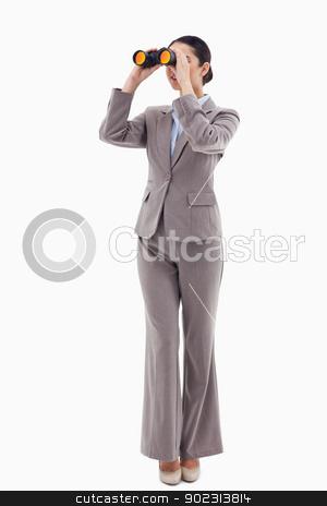 Portrait of a brunette businesswoman looking through binoculars stock photo, Portrait of a brunette businesswoman looking through binoculars against a white background by Wavebreak Media
