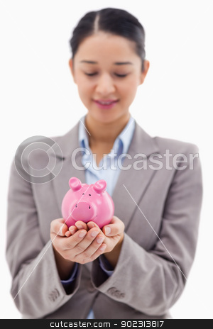 Portrait of a young businesswoman holding a piggy bank stock photo, Portrait of a young businesswoman holding a piggy bank against a white background by Wavebreak Media